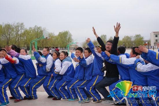 """安徽师范大学研究生支教团成员在灵台二中开展""""大手拉小手,我们一起走""""为主题的户外素质拓展活动。"""