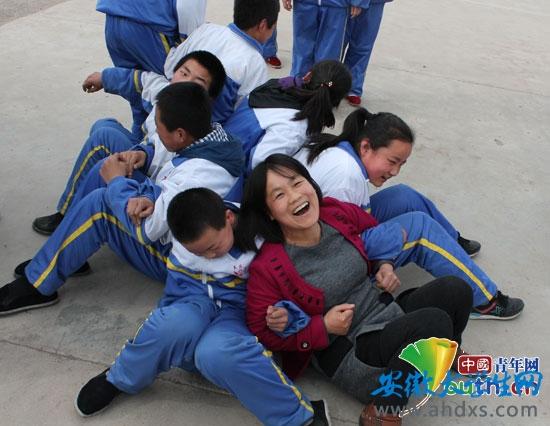 """安徽师范大学支教团成员与灵台二中学生在操场上开展""""坐地起身""""素质拓展活动。"""