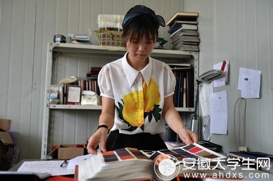 90后女大学生王颖毕业即创业,图为她正在厂房内为笔记本挑选封面的颜色。