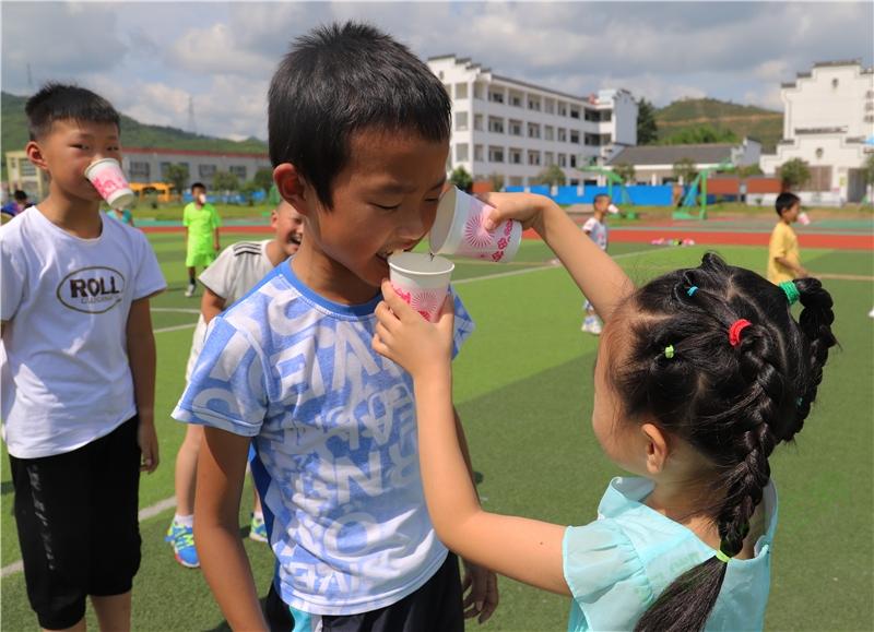 """安徽师大学子赴溪口:践行""""阳光体育"""",开设趣味运动孩子们排队开始""""传水"""",小女孩把自己水杯中的水传给队友。第一轮游戏小男孩有些紧张,皱着眉头害怕纸杯掉下来。"""