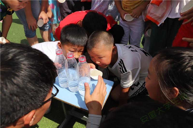 """""""纸杯传水""""游戏结束,孩子们聚在一起评判游戏结果。到底是哪一组运水最多呢?看起来很难判断,孩子们仔细地比较。"""