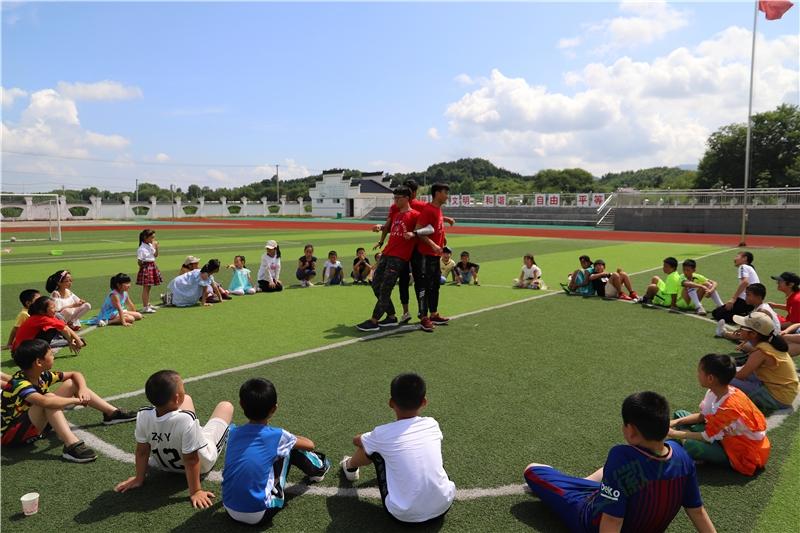 """趣味运动会第二个游戏""""坐地起身"""",孩子们需要借助彼此的力量站起来,为了让孩子们明白游戏成功的关键在于同伴间的相互配合,志愿者们先身示范,孩子们围成一圈认真聆听,个个都跃跃欲试。"""