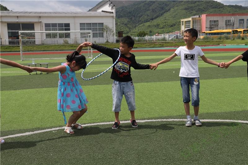 """""""能量传递""""游戏考验的就是团队协作能力,小男孩努力想把""""能量环""""传给下一个小女孩,小女孩配合他弯下身子,马上就要钻进""""能量圈""""中啦!"""