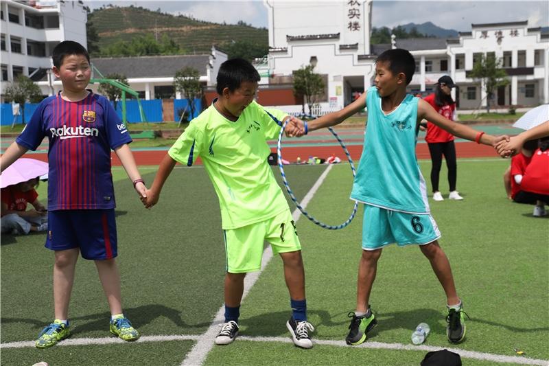 """在传递""""能量环""""的过程中,两位穿球衣的小朋友是搭档了好几年的""""球友"""",轻而易举地就钻过了""""能量环"""",两人相视一笑,这正是长久合作的默契。"""